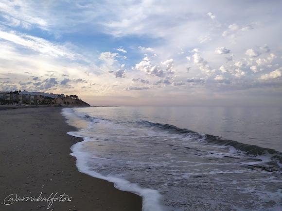 Amanecer en la Playa de La cala del Moral, al fondo El Cantal