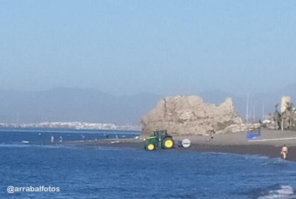 Tractor en La Cala del Moral para señalización de la playa por frnjas para marcar las distancias en verano de 2020 durante la crisis del Coronavirus